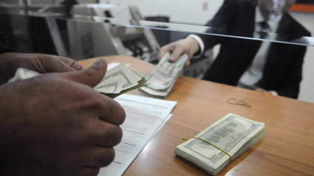 An employee of a money changer counts U.S. dollar notes for a customer at a bank in Cairo